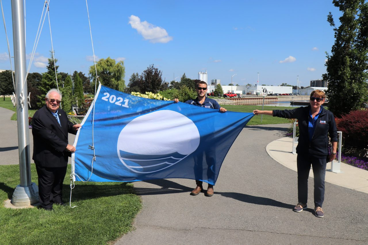 Quinte West Mayor Jim Harrison, Assistant Manager Andrew Belej, and Marina Manager Kathy Lammer raise the 2021 Blue Flag